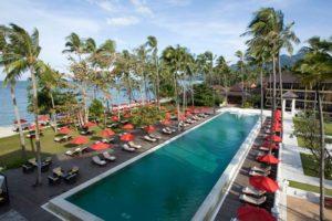 Укрытая пышной зеленью южная сторона пляжа представляет собой более узкую полосу песка, на которой выстроились красные зонтики шикарного курорта The Amari Emerald Cove Koh Chang.