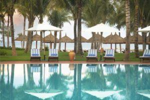 Бассейн отеля Vinpearl Phu Quo с шезлонгами и зонтами.