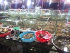 Свежайшие креветки, крабы, гребешки, омары, рыба и другая живность типа лягушек, черепах и змей, находятся в аквариумах с водой.