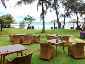 Пляж отеля с зеленой лужайкой.